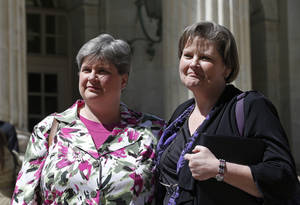 Photo - Plaintiffs challenging Oklahoma's gay marriage ban Sharon Baldwin, left, and her partner Mary Bishop leave court following a hearing at the 10th U.S. Circuit Court of Appeals in Denver, Thursday, April 17, 2014. The appeal of a lower court's January ruling that struck down Oklahoma's gay marriage ban is the second time the issue has reached appellate courts since the U.S. Supreme Court shook up the legal landscape last year by finding the federal Defense of Marriage Act was unconstitutional. (AP Photo/Brennan Linsley)