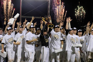 Photo - Vanderbilt coach Tim Corbin holds the trophy as he celebrates with his players after Vanderbilt defeated Virginia 3-2 in the deciding game of the best-of-three NCAA baseball College World Series finals in Omaha, Neb., Wednesday, June 25, 2014. (AP Photo/Eric Francis)