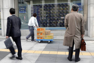 Photo - Pedestrians look at an electronic stock board of a securities firm in Tokyo, Friday, Jan. 25, 2013.  Japan's benchmark stock index jumped about 2 percent Friday after the country's currency continued to slide against the dollar. (AP Photo/Koji Sasahara)