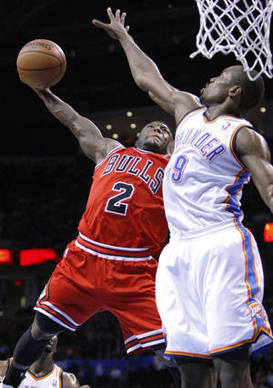 Photo - Chicago Bulls guard Nate Robinson (2) goes up for a dunk over Oklahoma City Thunder forward Serge Ibaka (9) during the second quarter of an NBA basketball game in Oklahoma City, Sunday, Feb. 24, 2013. (AP Photo/Alonzo Adams)