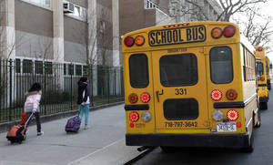 Photo - School buses wait to drop off children at school in New York, Wednesday, Feb. 20, 2013. New York City school bus drivers who serve 152,000 children were back at work Wednesday after a monthlong strike.  Regular schedules resumed on all 7,700 routes serving the nation's largest public school system. Five thousand of those routes were affected by the strike. The city has about 1.1 million children in public schools. (AP Photo/Seth Wenig)