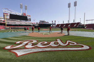 Photo - The Cincinnati Reds grounds crew checks the field on Sunday, March 30, 2014, in Cincinnati. The Reds host the St. Louis Cardinals, Monday afternoon in their Opening Day baseball game. (AP Photo/Al Behrman)