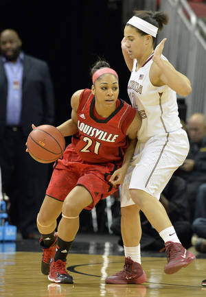 Photo - Louisville's Bria Smith, left, attempts to drive around the defense of Florida State's Brittany Brown during the first half of their NCAA college basketball game on Sunday, Nov. 24, 2013, in Louisville, Ky. (AP Photo/Timothy D. Easley)
