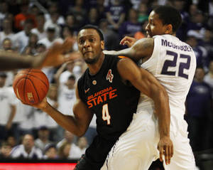 Photo - Oklahoma State guard Brian Williams (4) looks to pass while covered by Kansas State guard Rodney McGruder (22) during the first half of an NCAA college basketball game Saturday, March 3, 2012, in Manhattan, Kan. (AP Photo/Orlin Wagner) ORG XMIT: KSOW103