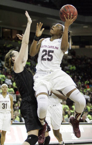 Photo - South Carolina's Tiffany Mitchell (25) drives for the basket as Missouri's Joday Frericks tries to block during the first half of an NCAA college basketball game on Sunday, Feb. 2, 2014, in Columbia, S.C. South Carolina won 78-62. (AP Photo/Mary Ann Chastain)