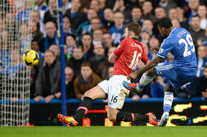 Photo - Chelsea's Samuel Eto'o, right, scores past Manchester United Michael Carick to score first goal of the game during their English Premier League soccer match at Stamford Bridge, London Sunday Jan. 19, 2014. (AP Photo/Andrew Matthews/PA) UNITED KINGDOM OUT