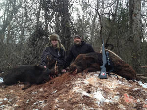 Photo - Jeff Puckett of Norman and his 13-year-old daughter, Abby, pose with two feral hogs they shot earlier this month at Hog Wild Outfitters near Criner. <strong>Photo provided</strong>
