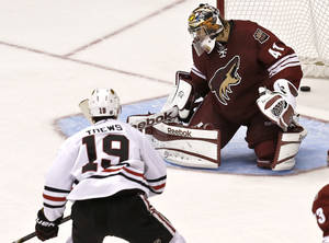 photo - Chicago Blackhawks&#039; Jonathan Toews (19) beats Phoenix Coyotes&#039; Mike Smith (41) for a goal during the second period in an NHL hockey game Thursday, Feb. 7, 2013, in Glendale, Ariz.(AP Photo/Ross D. Franklin)