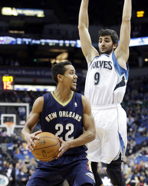 Photo - New Orleans Pelicans' Brian Roberts, left,  looks to pass as Minnesota Timberwolves' Ricky Rubio of Spain hovers over him in the first quarter of an NBA basketball game, Wednesday, Jan. 29, 2014, in Minneapolis. (AP Photo/Jim Mone)