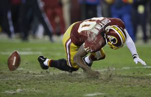 photo - Washington Redskins quarterback Robert Griffin III falls after twisting his knee while reaching for a loose ball during the second half of an NFL wild card playoff football game against the Seattle Seahawks in Landover, Md., Sunday, Jan. 6, 2013. (AP Photo/Matt Slocum)