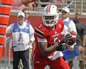 Photo - Louisville quarterback Teddy bridgewater rolls out looking to pass against Eastern Kentucky in a NCAA college football game in Louisville, Ky., Saturday, Sept. 7, 2013. Bridgewater led Louisville to a 44-7 victory. (AP Photo/Garry Jones)