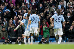 Photo - Manchester City's Fernandinho, top left, celebrates with teammates after scoring against Arsenal during their English Premier League soccer match at the Etihad Stadium, Manchester, England, Saturday Dec. 14, 2013. (AP Photo/Jon Super)