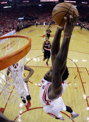 Photo - Houston Rockets' Patrick Beverley goes up for a dunks during the first half in Game 1 of an opening-round NBA basketball playoff series against the Portland Trail Blazers, Sunday, April 20, 2014, in Houston. (AP Photo/David J. Phillip)