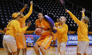 Photo - Tennessee center Mercedes Russell runs a gauntlet that includes head coach Holly Warlick, right, and assistant coach Dean Lockwood, second from right, during practice for an NCAA women's college basketball game Friday, March 21, 2014, in Knoxville, Tenn. Tennessee will face Northwestern State in a first-round playoff game Saturday. (AP Photo/Mark Humphrey)