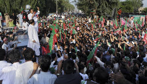 Photo -   Pakistan's ex-cricket star-turned-politician Imran Khan, top left, addresses supporters during a peace march in Mianwali, Pakistan, Saturday, Oct. 6, 2012. Thousands of Pakistanis joined by a group of U.S. anti-war activists headed toward Pakistan's militant-riddled tribal belt Saturday to protest U.S. drone strikes - even as a Pakistani Taliban faction warned that suicide bombers would stop the demonstration. (AP Photo/Jabbar Ahmed)