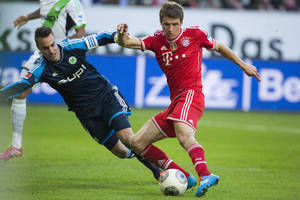 Photo - Bayern's Thomas Mueller, right, scores his side's 2nd goal against Wolfsburg goalkeeper Diego Benaglio of Switzerland during the German Bundesliga soccer match between VfL Wolfsburg and Bayern Munich in Wolfsburg, Germany, Saturday, March 8, 2014. (AP Photo/Gero Breloer)