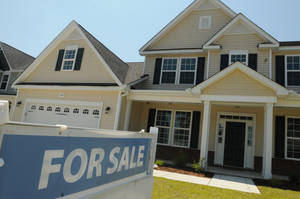 Photo - FILE - This June 19, 2014, file photo, shows a home for sale in Wilmington, N.C.  Real estate data provider CoreLogic reports on U.S. home prices in July. In June, prices rose by the smallest year-over-year amount in 20 months, slowed by modest sales and more properties coming on the market. The slowing increases should make homes more affordable after prices had risen sharply last year. At the same time, Americans' pay hasn't risen nearly as fast. (AP Photo/Wilmington Star-News, Ken Blevins, File)