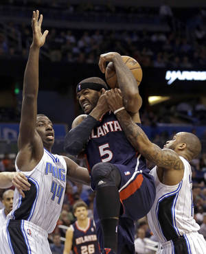 Photo - Atlanta Hawks' Josh Smith (5) is fouled as he drives to the basket between Orlando Magic's Andrew Nicholson (44) and Jameer Nelson, right, during the first half of an NBA basketball game, Wednesday, Feb. 13, 2013, in Orlando, Fla. (AP Photo/John Raoux)