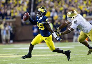 Photo - Michigan quarterback Devin Gardner (98) escapes a tackle from Notre Dame defensive lineman Stephon Tuitt (7) in the second quarter of an NCAA college football game, in Ann Arbor, Mich., Saturday, Sept. 7, 2013. (AP Photo/Tony Ding)