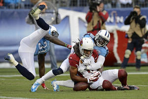 Photo - Arizona Cardinals wide receiver Larry Fitzgerald (11) can't hang onto a pass as he is defended by Tennessee Titans cornerback Jason McCourty (30) and safety Bernard Pollard (31) in the second quarter of an NFL football game Sunday, Dec. 15, 2013, in Nashville, Tenn. (AP Photo/Mark Zaleski)