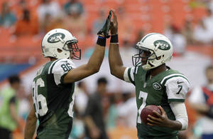 Photo - New York Jets quarterback Geno Smith (7) gives a high-five to teammate David Nelson (86) before the last play against the Miami Dolphins in the fourth quarter of a NFL football game in Miami Gardens, Fla., Sunday, Dec. 29, 2013. The Jets won 20-7. (AP Photo/Alan Diaz)