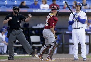 photo - Home plate umpire Chris Segal, left, gestures a called strike on New York Mets' Travis d'Arnaud, right, for the final out, next to Venezuela catcher Miguel Montero in anexhibition baseball game, Wednesday, March 6, 2013, in Port St. Lucie, Fla. Venezuela won 14-10. (AP Photo/Julio Cortez)
