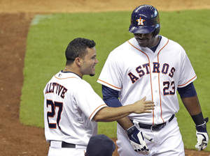 Photo - Houston Astros' Chris Carter (23) is congratulated by Jose Altuve (27) after hitting a solo home run against the Arizona Diamondbacks in the fourth inning of a baseball game Wednesday, June 11, 2014, in Houston. (AP Photo/Pat Sullivan)