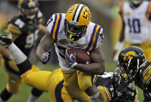 Photo - LSU running back Jeremy Hill (33) rushes through the Iowa defense, including defensive back Desmond King, right, to score on a 14-yard touchdown run during the second quarter of the Outback Bowl NCAA college football game Wednesday, Jan. 1, 2014, in Tampa, Fla. (AP Photo/Chris O'Meara)