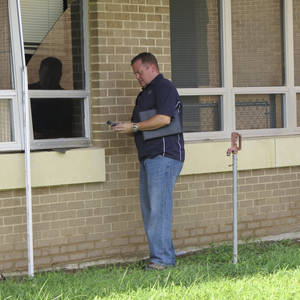 Photo -  An unidentified worker examines damage from an August 2013 underground water pipe break at Parker Intermediate School in McAlester.  <strong> Provided  -  Provided </strong>