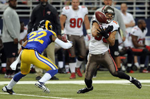Photo - Tampa Bay Buccaneers wide receiver Vincent Jackson, right, bobbles the ball before catching it for a 19-yard gain as St. Louis Rams cornerback Trumaine Johnson watches during the second quarter of an NFL football game on Sunday, Dec. 22, 2013, in St. Louis. (AP Photo/L.G. Patterson)