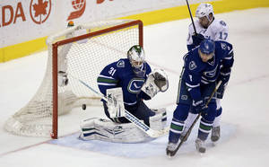 Photo - Vancouver Canucks goalie Eddie Lack, left, of Sweden, allows a goal to Tampa Bay Lightning's Valtteri Filppula, not seen, while being screened by Alex Killorn, top right, as Canucks' Chris Tanev defends during the second period of an NHL hockey game Wednesday, Jan. 1, 2014, in Vancouver, British Columbia. (AP Photo/The Canadian Press, Darryl Dyck)