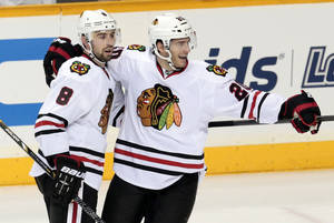 Photo - Chicago Blackhawks defenseman Nick Leddy (8) celebrates with Brandon Saad after Leddy scored against the Nashville Predators in the second period of an NHL hockey game Tuesday, Dec. 17, 2013, in Nashville, Tenn. (AP Photo/Mark Humphrey)