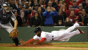 Photo - Boston Red Sox's Jackie Bradley Jr. dives home with the game-winning run on an infield single by teammate Xander Bogaerts as catcher Evan Gattis, left,  looks on during the ninth inning of their 4-3 win in a baseball game at Fenway Park, Thursday, May 29, 2014, in Boston. (AP Photo/Winslow Townson)