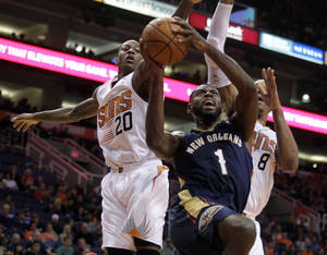 Photo - New Orleans Pelicans point guard Tyreke Evans (1) drives between Phoenix Suns shooting guard Archie Goodwin (20) and forward Channing Frye (8) in the second quarter during an NBA basketball game on Sunday, Nov. 10, 2013, in Phoenix. (AP Photo/Rick Scuteri)
