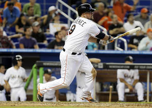 Photo - Miami Marlins' Casey McGehee hits a single to score Jeff Baker and Giancarlo Stanton in the eighth inning of a baseball game against the Colorado Rockies, Thursday, April 3, 2014, in Miami. The Marlins won 8-5. (AP Photo/Lynne Sladky)