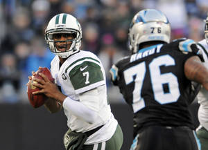 Photo - New York Jets' Geno Smith (7) looks to pass under pressure from Carolina Panthers' Greg Hardy (76) during the first half of an NFL football game in Charlotte, N.C., Sunday, Dec. 15, 2013. (AP Photo/Mike McCarn)