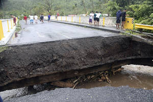 Photo - People walk over a destroyed bridge in Samoa's capital Apia, Friday, Dec. 14, 2012, after cyclone Evan ripped through the South Pacific island nation. The powerful cyclone flattened homes and uprooted trees with winds of up to 165 kilometers (100 miles) per hour. Phone lines, Internet service and electricity were down across the country, and the airport was closed.(AP Photo/Seti Afoa)