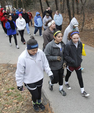 Photo - Bundled in layers to stay warm, walkers begin the fun walk and run at the Forever Edmond 5k.
