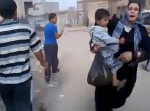 Photo -   This image taken from video obtained from Shaam News Network, which has been authenticated based on its contents and other AP reporting, shows a woman carrying a child running away from the scene of shelling in Qouriyeh, Syria, Friday, Nov. 9, 2012. (AP Photo/Shaam News Network via AP video)