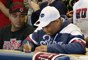 Photo - Heritage Hall's Markus Wakefield signs to play football at Howard University as teammate Quintaz Struble watches during the National Signing Day ceremony at Heritage Hall in Oklahoma City, Wednesday, Feb. 1, 2012. Photo by Nate Billings, The Oklahoman <strong>NATE BILLINGS</strong>