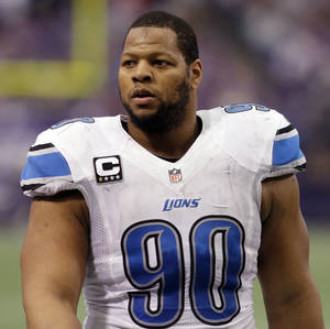 Photo - File- This Dec. 29, 2013, file photo shows Detroit Lions defensive tackle Ndamukong Suh walking on the field during the first half of an NFL football game against the Minnesota Vikings in Minneapolis.  A person familiar with the situation says Suh is not attending the Detroit Lions' voluntary minicamp this week. The person, who says Suh will attend the team's voluntary workouts in May and mandatory minicamp next month, spoke Monday April 21, 2014, to The Associated Press on condition of anonymity because Suh was not announcing his plans. (AP Photo/Jim Mone, File)