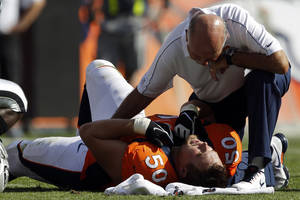 photo -   FILE - In this Sept. 30, 2012, file photo, Denver Broncos center J.D. Walton (50) is attended to by a trainer after being injured when Oakland Raiders defensive end Jack Crawford inadvertently crashed into his legs as he was making the tackle on running back Lance Ball during the second quarter of their NFL football game in Denver. The Broncos placed Walton on injured reserve with a broken and dislocated left ankle on Monday, Oct. 1. (AP Photo/David Zalubowski, File)