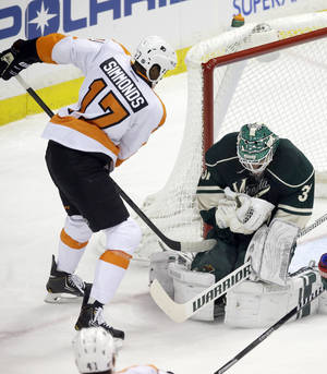 Photo - Minnesota Wild goalie Josh Harding, right, stops a shot by Philadelphia Flyers'  Wayne Simmonds in the first period of an NHL hockey game, Monday,  Dec. 2, 2013, in St. Paul, Minn. (AP Photo/Jim Mone)