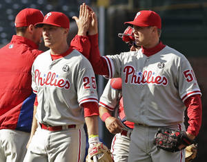 Photo - Philadelphia Phillies closer Jonathan Papelbon (58), right, celebrates with starter Cliff Lee after the Phillies defeated the Chicago Cubs 2-0 in a baseball game in Chicago, Saturday, April 5, 2014. (AP Photo/Nam Y. Huh)