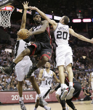 Photo - FILE - In this June 13, 2013 file photo, Miami Heat's LeBron James (6) passes between San Antonio Spurs' Boris Diaw (33), of France,  and Manu Ginobili (20), of Argentina, during the second half at Game 4 of the NBA Finals, in San Antonio.  A rematch of last year's thrilling NBA Finals finish is possible, but the Spurs and Heat would have to get through tough paths to get there. (AP Photo/Eric Gay, File)