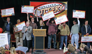 Photo -   FILE- In this Feb. 22, 2006, file photo, the eight winners of the $365 million Nebraska Powerball lottery hold up their ceremonial checks at a news conference in Lincoln, Neb. As the drawing for a $500 million Powerball jackpot approaches, Wednesday, Nov. 28, 2012, past winners of mega-lottery drawings and financial planners have some advice: stick to a budget, invest wisely, learn to say no and be prepared to lose friends while riding an emotional roller-coaster. (AP Photo/Nati Harnik, File)