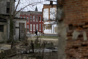 Photo - In this April 4, 2013 picture, a man walks past boarded up row houses and vacant lots in Baltimore. Baltimore has lost nearly a third of its population since it peaked in the 1950s, and today an estimated 16,000 buildings are vacant or abandoned. (AP Photo/Patrick Semansky)