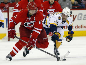 Photo - Carolina Hurricanes' Jordan Staal (11) squares off against Nashville Predators' Viktor Stalberg (25) during the second period of an NHL hockey game in Raleigh, N.C., Sunday, Jan. 5, 2014. (AP Photo/Karl B DeBlaker)