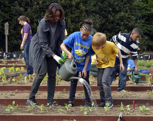 Photo - FILE - This April 2, 2014 file photo shows first lady Michelle Obama helping to hold a watering can after she and Friendship Public Charter Elementary School student Dynasty Meade, center, and Bancroft Elementary School student Silas Stutz, right, planted broccoli in the White House Kitchen Garden at the White House in Washington. The White House says tours of Michelle Obama's produce garden will be operating again soon. The tours were grounded after mandatory budget cuts went into effect last year. Public tours of parts of the White House also were halted due to the cuts but resumed after President Barack Obama signed legislation funding government operations. The garden tours are scheduled to resume the week of July 14. They are open to community and school groups that are interested in gardening and healthy eating. (AP Photo/Susan Walsh, File)