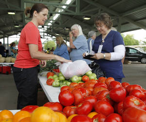 Photo -  Lynne Lusk purchases juicy red tomatoes from Darlene Hathurst, of Hathurst Farms, at the Edmond Farmers Market. PHOTO BY PAUL HELLSTERN, THE OKLAHOMAN  <strong>PAUL HELLSTERN -   </strong>